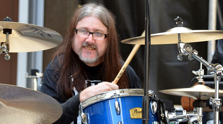 A man with long brown hair, a grey beard and glasses drums on his Pearl drumkit.