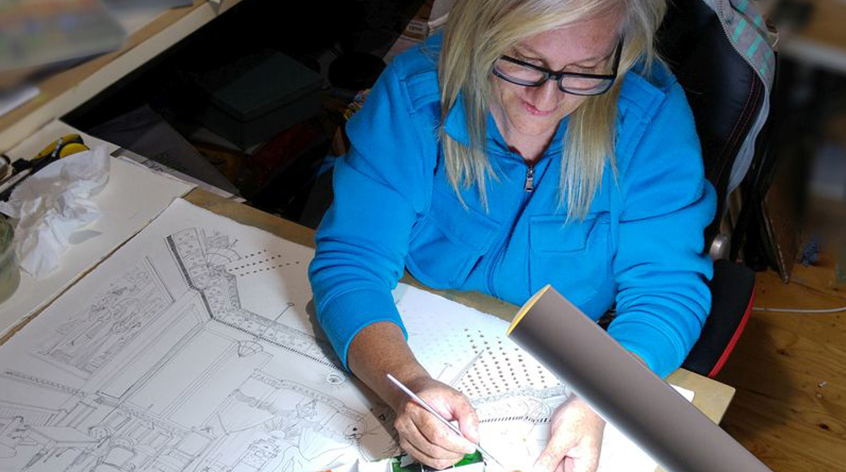 Images shows Chelle Destefano sitting at her desk and drawing.