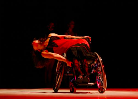 A dancer in a wheelchair is centre stage, her upper torso moving at right angles to the stage as she performs