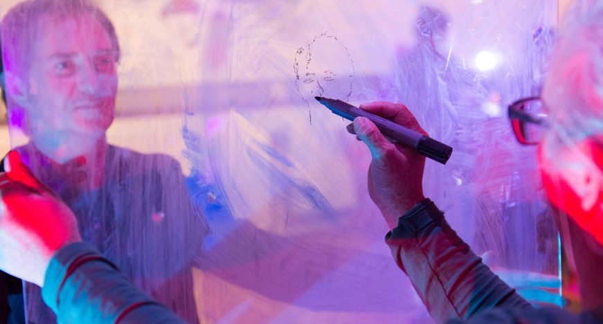 A sensory station at the Call and Response workshop. A piece of clear glass separates Australian visual artist Chelle Destefano and Rudely Interrupted's Rohan Brooks. Chelle draws Rohan's portrait on the glass
