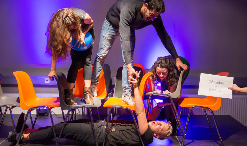 "A sensory station at the Call and Response workshop. Four artists interact with each other through theatre, using chairs as props. Two artists stand on top of chairs while one leans over a chair and another lies underneath. Someone holds a sign saying ""Education"" in English and in German."