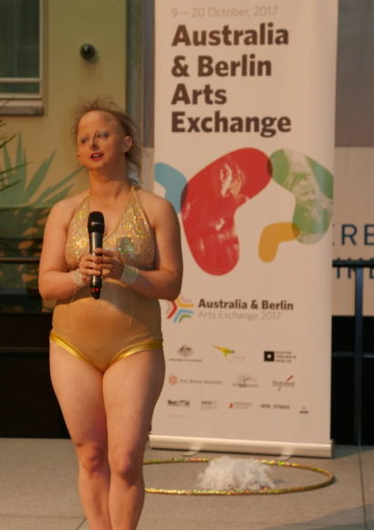 Sarah Houbolt stands on stage with a microphone in her hand. In the background is a banner reading, Australia and Berlin Arts Exchange