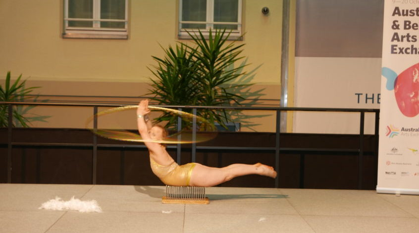Sarah Houbolt spins a hula hoop around one outstretched arm while lying on a bed of nails.
