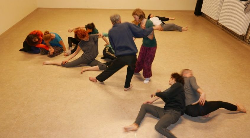 Five pairs of dancers move together in the studio space. In the foreground, Anna Seymour is partnered with a woman. They pose mid-roll on the floor, back to back. In the middle is Bernahd and his partner, standing together with arms connected and each with one leg pointed out. Three other dance partners pose in the background in various mirroring poses.