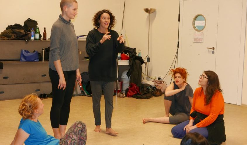 Ana Seymour stands in the centre of a small group of dancers in a Dance Studio at Ufer studios, she wears a black jumper and grey sweat pants. Standing next to her on the right, is a female dancer wearing a grey jumper and black sweat pants, she is facing Ana. Three dancers sit on the floor around Ana, looking up at her as she teaches, in the background jackets, bags, drink bottles and other personal items are randomly place on storage drawers near the entrance to the room, where class members left them on entry.