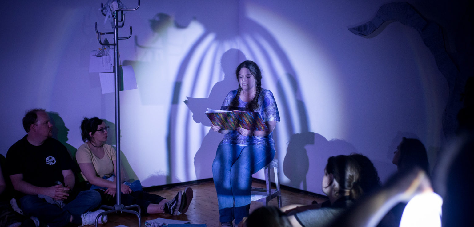 A woman sits on a chair in the corner of a room, reading aloud from a book. Several people sit on the floor, listening. A shadow of a large cage is cast over the reader.