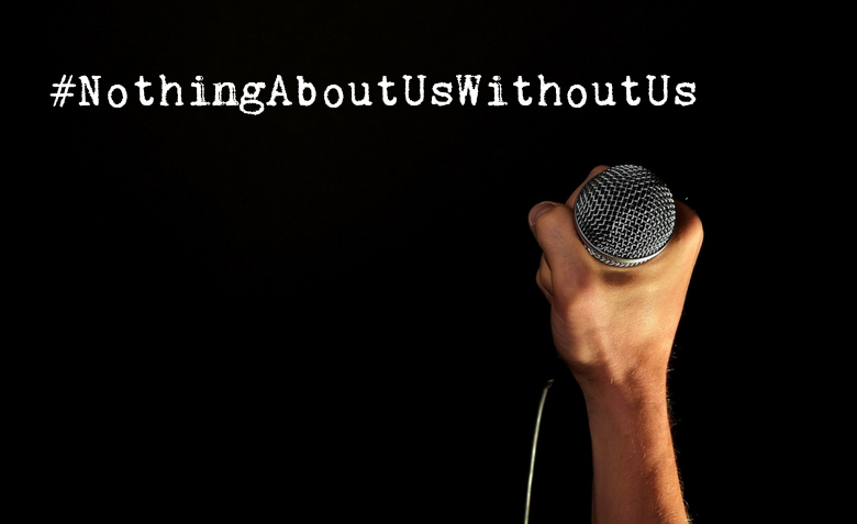 On a black background, a hand holds up a microphone. In white text, it reads: #NothingAboutUsWithoutUs