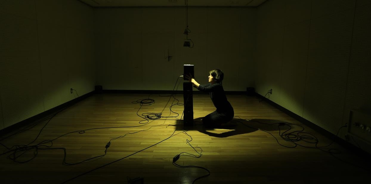 A woman dressed in black kneels in front of a tall speaker in the centre of a room. There is a spotlight on her. In all directions, cords run from the speaker into outlets in the wall.