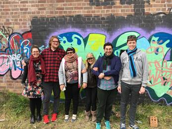 A group of six people stand in front of a wall with graffiti on it.