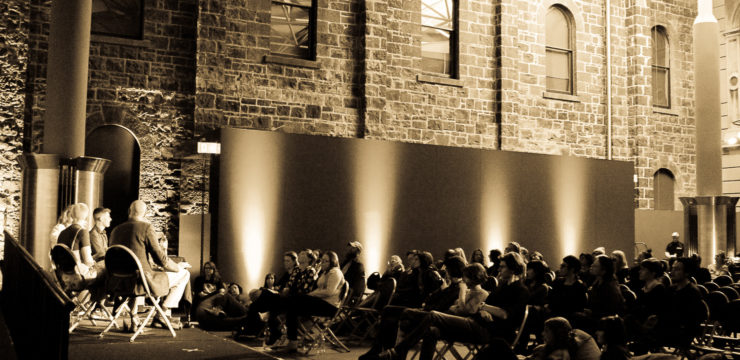 Sepia-toned photograph of an audience staged in an old hall, watching four people on stage in directors chairs.