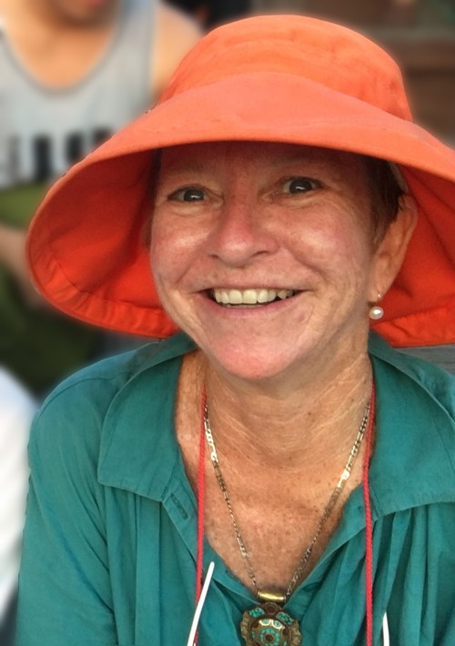 Jenine Mackay, smiling and wearing an orange hat and a teal blouse