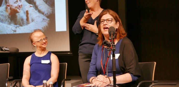 Sarah Houbolt and Meagan Shand sit on stage. Meagan speaks into a microphone while Sarah smiles. Behind them, an interpreter stands and signs. There is a screen displaying an image of Sarah performing.