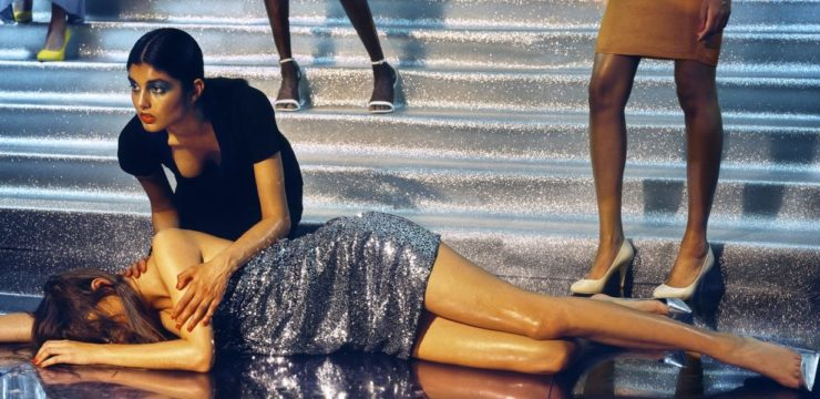 A female model crouches in concern over another model who lies on the floor, hair over her face, as if she has just fallen. Behind them is set of stairs. The legs and shoes of other models standing on the stairs are visible.