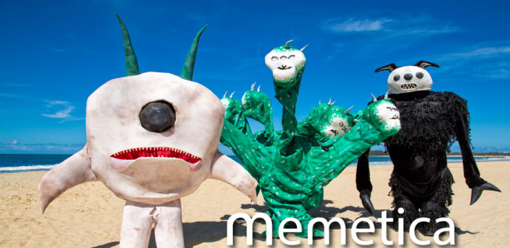 Three giant puppet monsters stand on the beach. On the left is a white round monster, in the middle is a green monster with multiple heads, and on the right is a black monster.