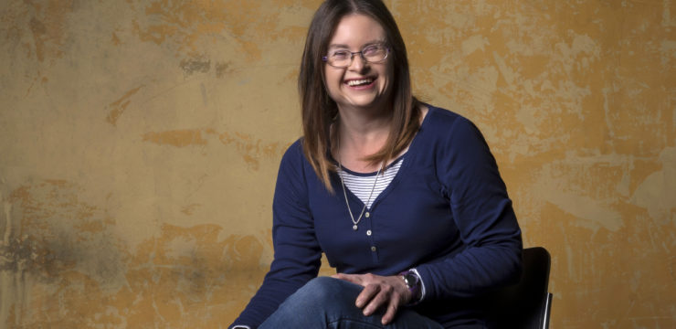 Photo of a woman sitting on a high chair in front of a textured wall. She has her legs crossed and wears glasses and a blue jumper, and has long brown hair.