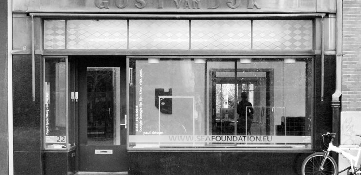 Black and white photo of a shopfront. A bike leans against the wall, and above the shop front in old lettering are the words GUST van DUKE. There is a big window with the lettering, SEA Foundation.