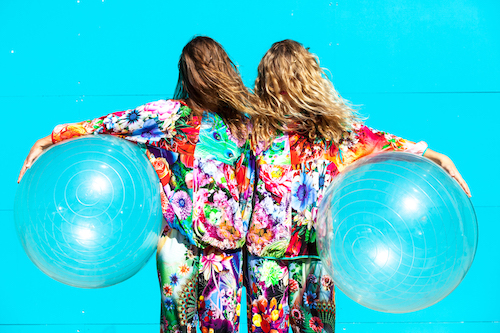 Two women stand with their backs to the camera in a mirror-image style pose. They are both wearing very colourful matching pyjama-style outfits and have long hair worn out, and under each arm (mirror image style) hold a large inflated clear ball..