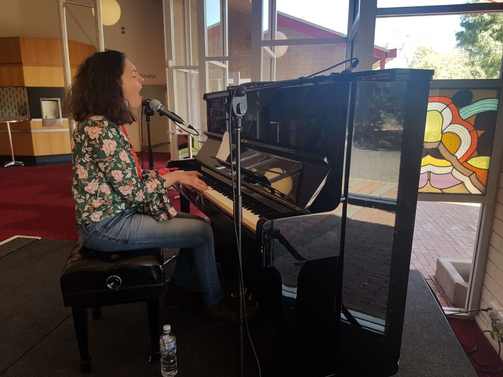 A woman plays a piano and sings. She has shoulder length curly hair and wears jeans and a floral blouse.