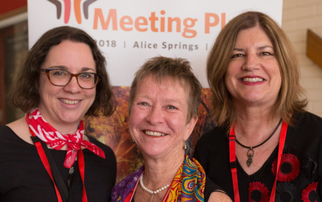 Three women stand in front of a Meeting Place banner, smiling at the camera.