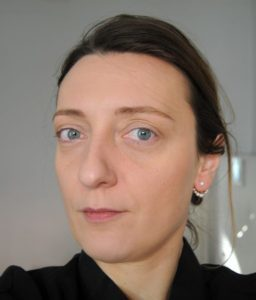 A woman in her late twenties looks to the camera with a serious expression. She has vivid blue eyes and brown hair pulled back.