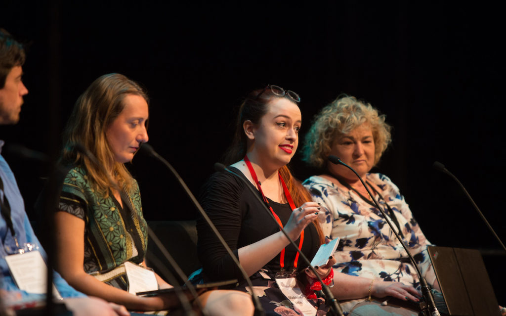 Four people sit on stage with miicrophones in front of them. In the middle, in focus, is a lady with long red hair pulled back, bright red lipstick. She is in her twenties. She is speaking while the others listen.
