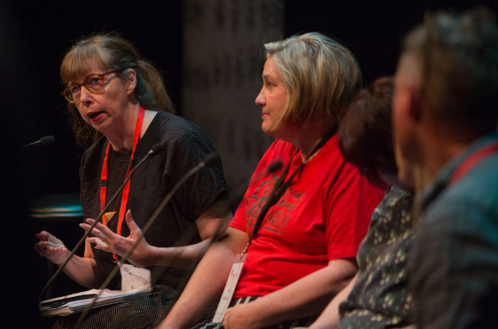 Three women sit on stage with microphones in front of them. The far woman wears a red lanyard, black top, adn speaks into the microphone while the others listen.