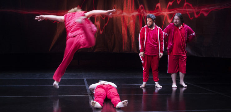 Image shows four dancers on stage, mid-performance. The four performers are dressed in red, and the stage is black with a red and black background. Two dancers stand next to each other and watch as a dancer leaps over another dancer, who is lying on the floor.