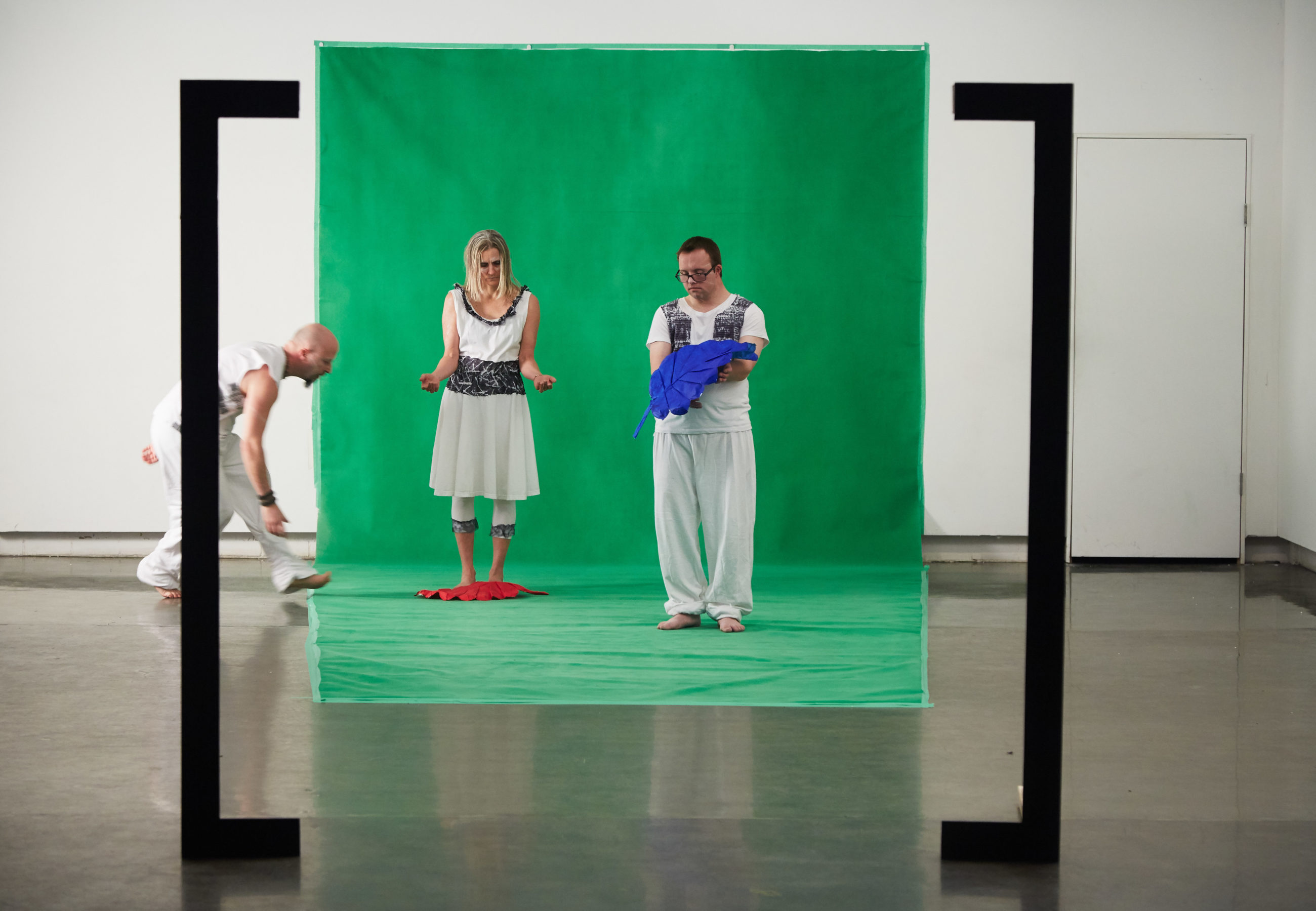 Image shows an art performance happening in a studio space. A female and male performer stand against a green backdrop, facing the camera. There are two large black lines in the foreground, marking out a focal point around the green screen, as if the audience is viewing through a camera lens. The man holds a large blue leaf. There is a large red leaf at the feet of the woman. Another male performer is in the process of walking into the focal point, into the green space.