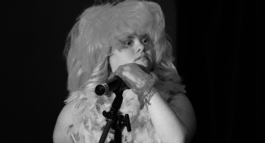 a black and white photo of a person wearing a wig and feathered boa holding a microphone