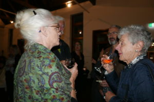 Two women with grey hair talk in the foreground, holding glasses of wine. In the background a number of other people stand and drink wine.