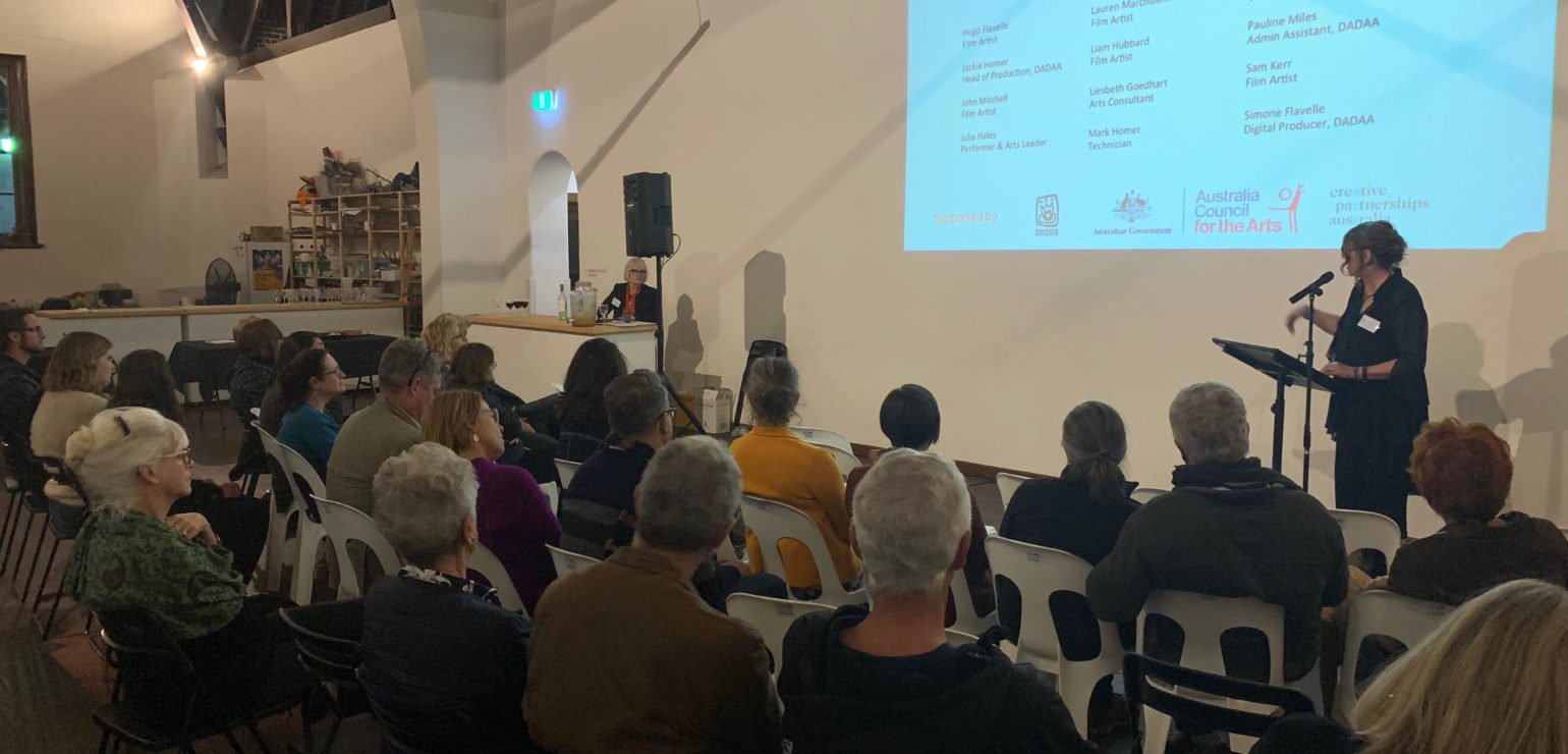 About 30 people sit on chairs in a hall. They look at the wall onto which a screen is projected with the Arts Access Australia logo. A woman in her 50s (Meagan Shand) speaks into a microphone.