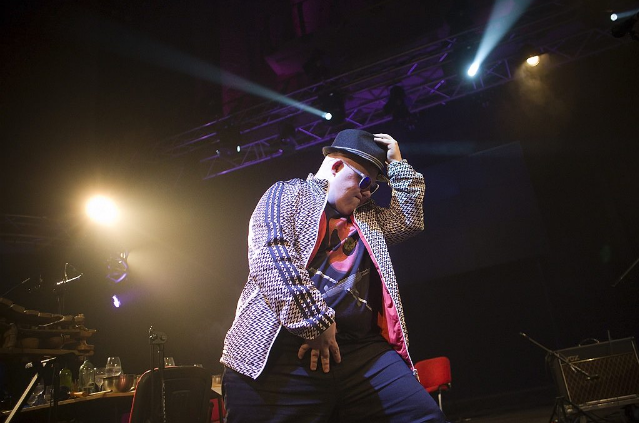 A man strikes a pose on stage, one hand to his hat. Behind him are stage lights shining