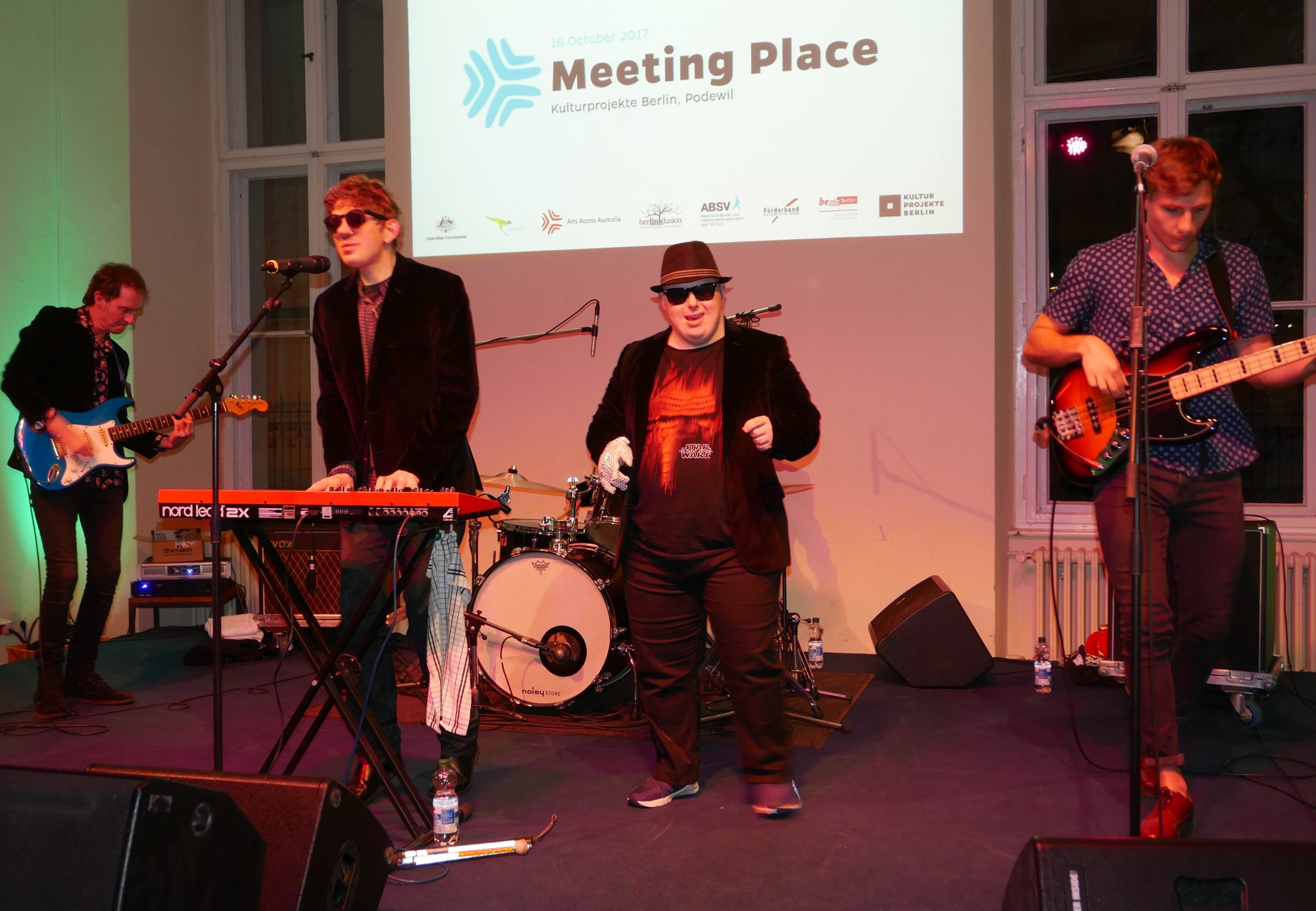 Four musicians perform on stage in a band below a sign that reads Meeting Place.