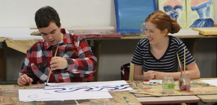 A man in his twenties paints at a desk alongside a woman with red hair, also in her twenties. She is looking over at him and smiling.