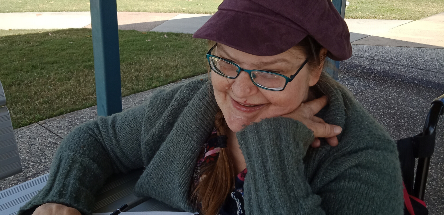 A lady in her forties is seated in her wheelchair at a picnic table, smiling gently. The lady is wearing teal glasses and a maroon capped beret like those worn by artists in Europe. She holds a pencil and a sketchbook is open in front of her.
