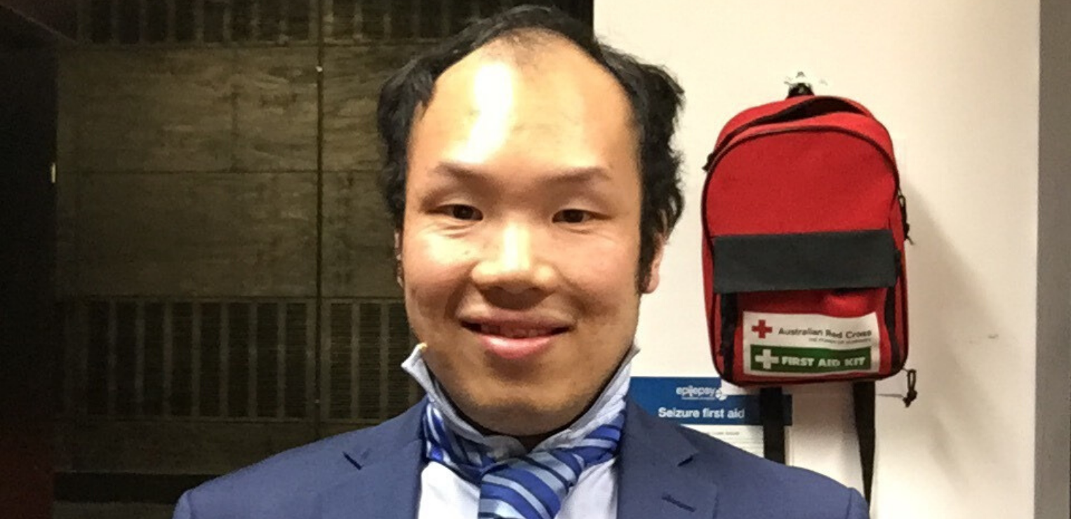A young man of Asian heritage smiles at the camera. He wears a blue suit with a blue and white striped tie.