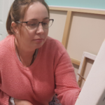 A woman aged in her late 30's wearing glasses, in a pink jumper sitting in her wheelchair. Her hair is tied back and she is looking at a canvas and holding her paintbrush.