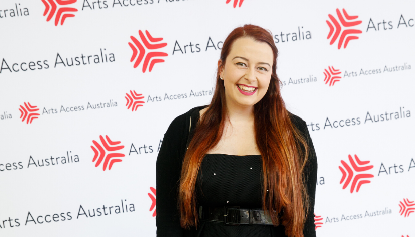A woman in her 20s with long red hair and a black dress stands in front of a photo board that features the Arts Access Australia logo