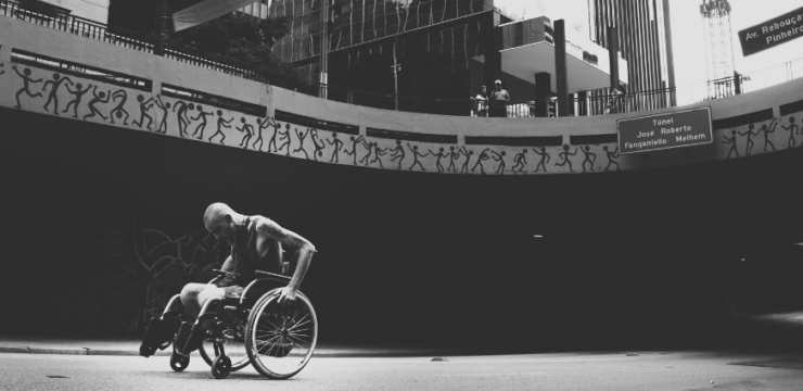 A black and white photo of a man using a manual wheelchair in an urban environment.