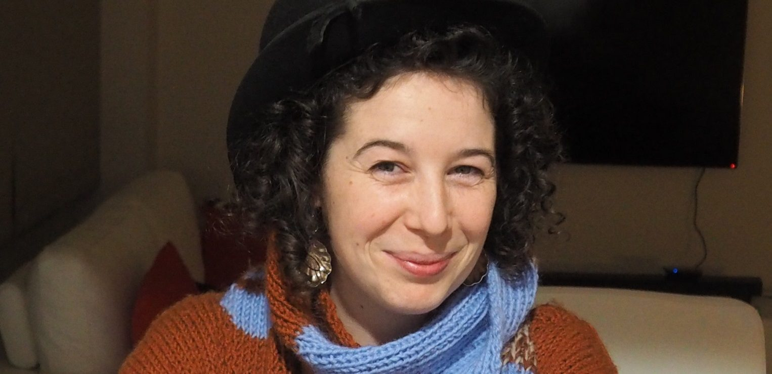 Prue Stevenson, smiling with curly hair, spoon earrings, a knitted scarf and jumper