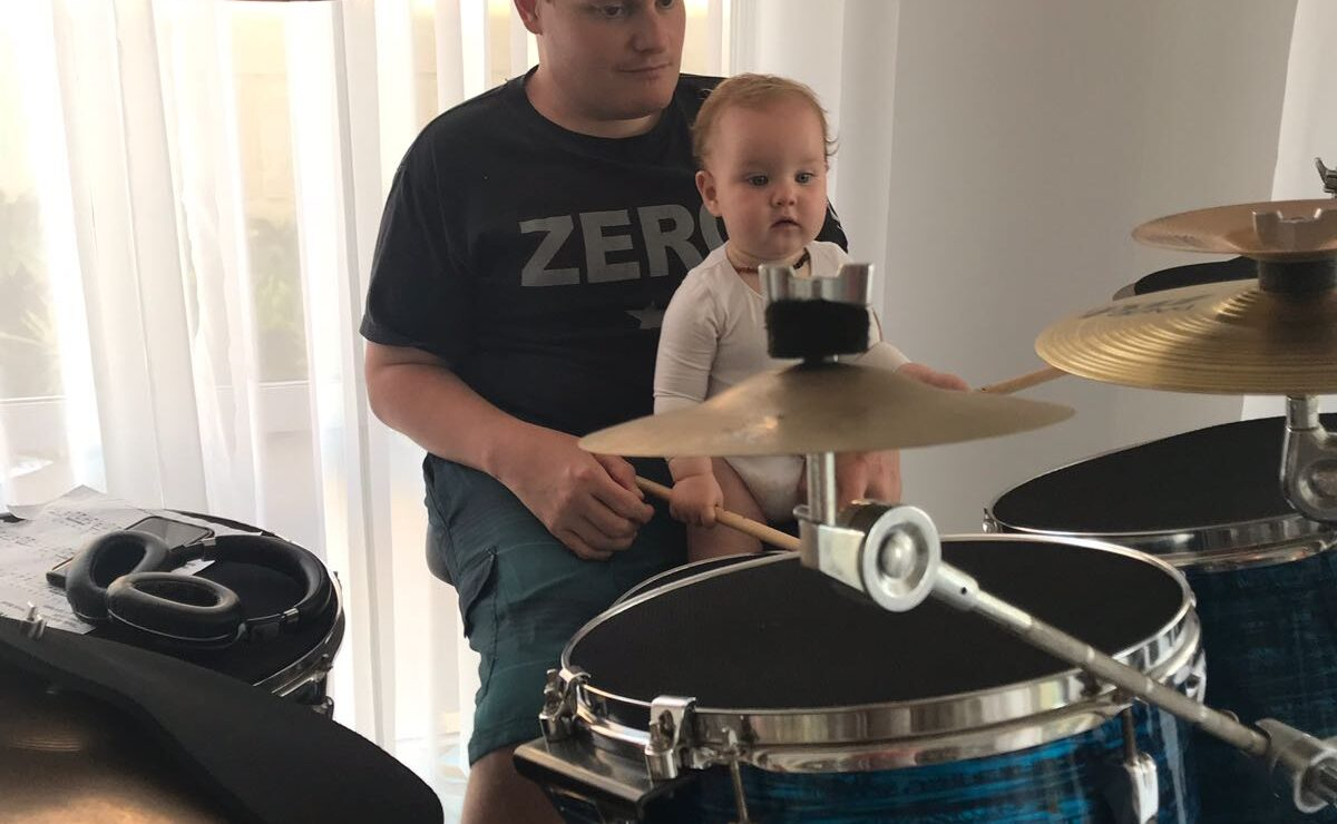 A caucasian male sits at a drum kit with a baby on his lap. The baby is holding the drum sticks.