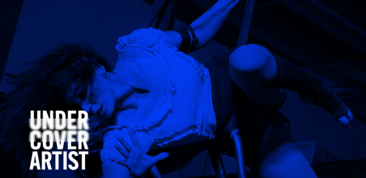 A woman performs on stage, her body suspended in a dance movement, face obscured by her hair. The image is masked with royal blue filter and overlaid is the Undercover Artist Festival in white.
