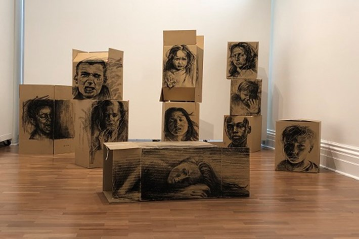 Gallery image of an art installation. Charcoal or blank ink sketched portraits are drawn on large brown cardboard boxes. The cardboard boxes are stacked in piles, with some lying down on their own.