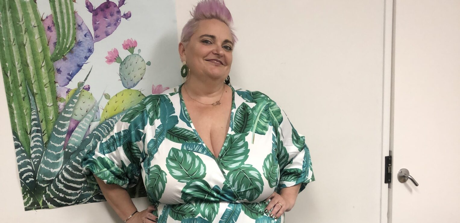 White curvy woman with pink hair wearing a long dress with a leaf foliage print.