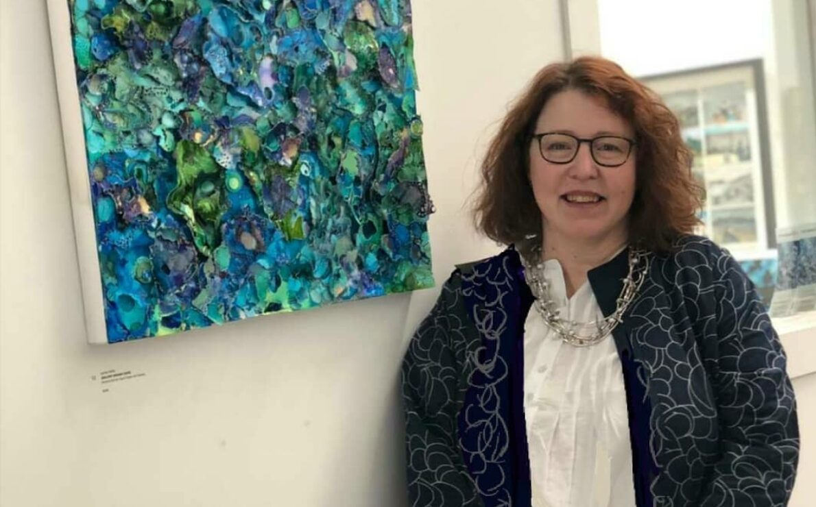 A white skinned woman in her 50's, red/brown shoulder length curly hair, glasses, smiling at the camera while standing in front of a green, blue artwork.