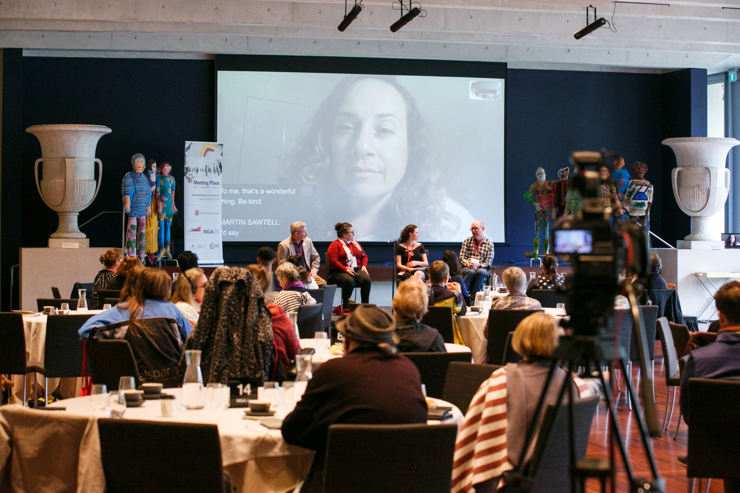 A conference room with people seated at round tables looking towards a stage. On the stage sits four people. Behind them is a large screen with a woman on a video call projected onto it. In the foreground on the right is a film camera on a tripod, filming the panel discussion.