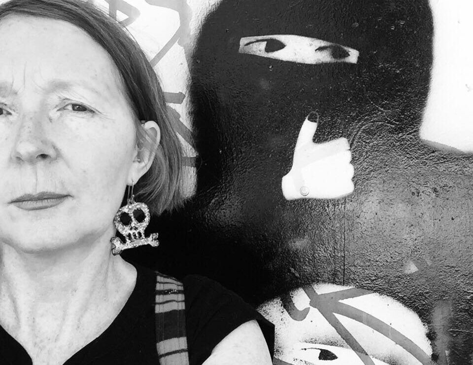 The image is black and white. A woman with a short bob wearing a skull earring, looks out at the viewer. She is standing in front of street art of a hooded figure with eyes showing giving a thumbs up.